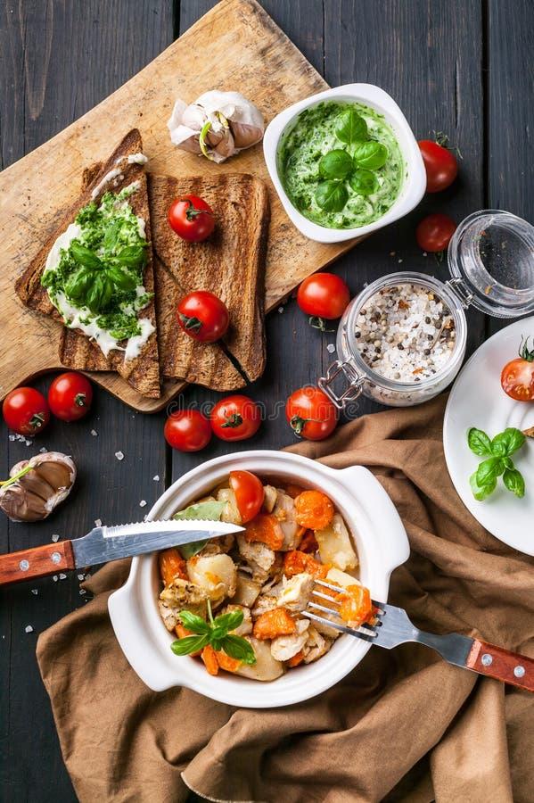 Patatas cocidas con la carne y zanahorias del pollo, bocadillos con queso y tomates de cereza en un fondo de madera oscuro Visi?n fotos de archivo libres de regalías