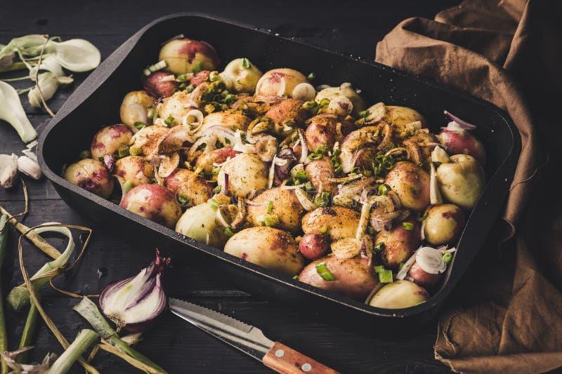 Patatas cocidas con las cebollas, el ajo y las especias en un fondo rústico oscuro Primer imagen de archivo