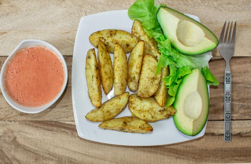 Patatas cocidas con las especias, curry y azafrán, con la salsa de tomate y el aguacate imagen de archivo