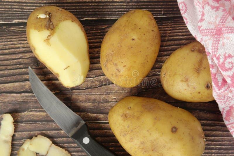 Patatas crudas en curso de peladura fotos de archivo