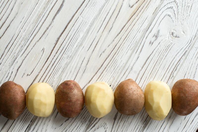 Patatas crudas frescas en un viejo fondo blanco de madera ligero Visión superior imagen de archivo libre de regalías