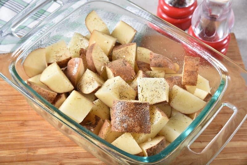 Patatas cubicadas en un plato de la hornada fotografía de archivo libre de regalías