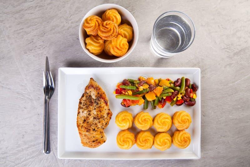 Patatas de oro de la duquesa con el pollo asado a la parrilla y las verduras mexicanas fotografía de archivo libre de regalías