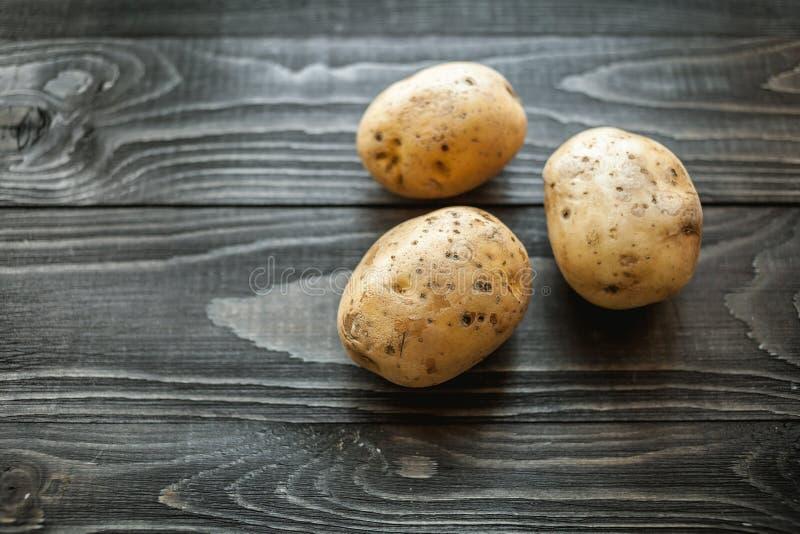 Patatas en fondo rústico de madera imágenes de archivo libres de regalías