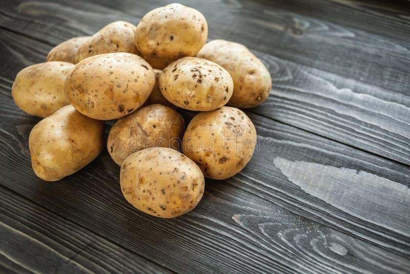 Patatas en fondo rústico de madera fotografía de archivo