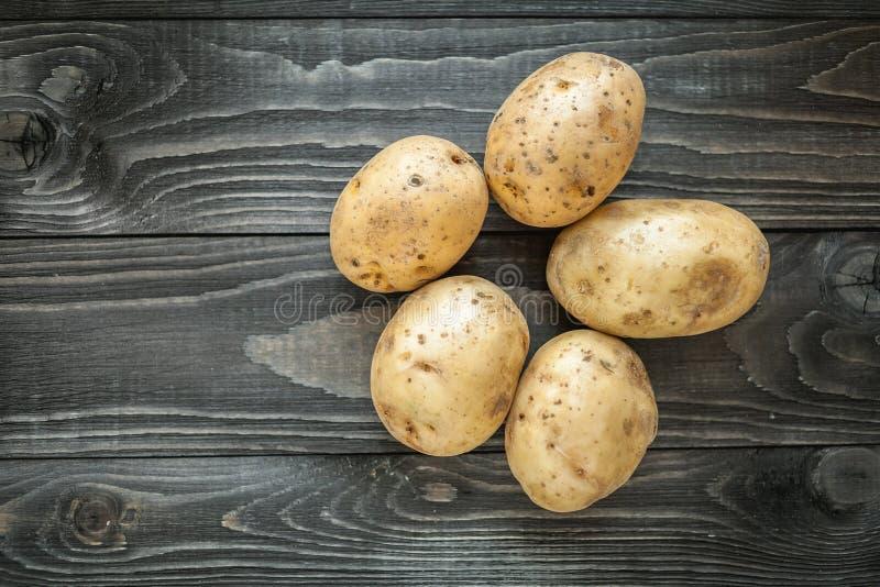 Patatas en fondo rústico de madera fotos de archivo