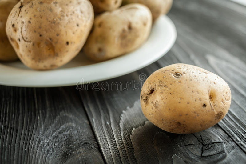 Patatas en fondo rústico de madera imagen de archivo