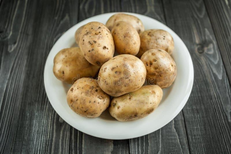 Patatas en fondo rústico de madera foto de archivo