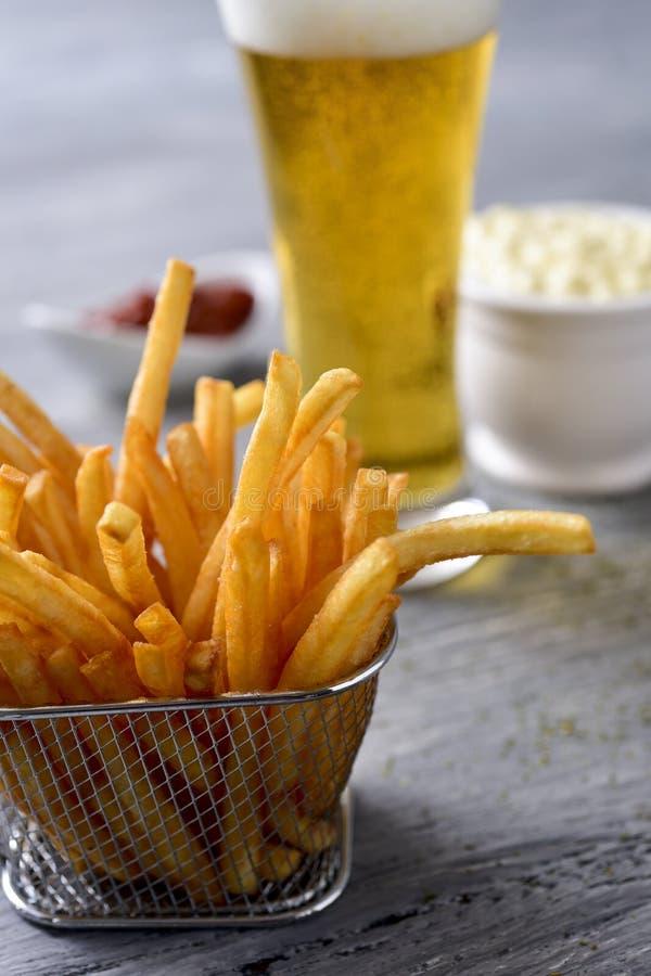 Patatas fritas, cerveza, mayonesa y salsa de tomate imagenes de archivo