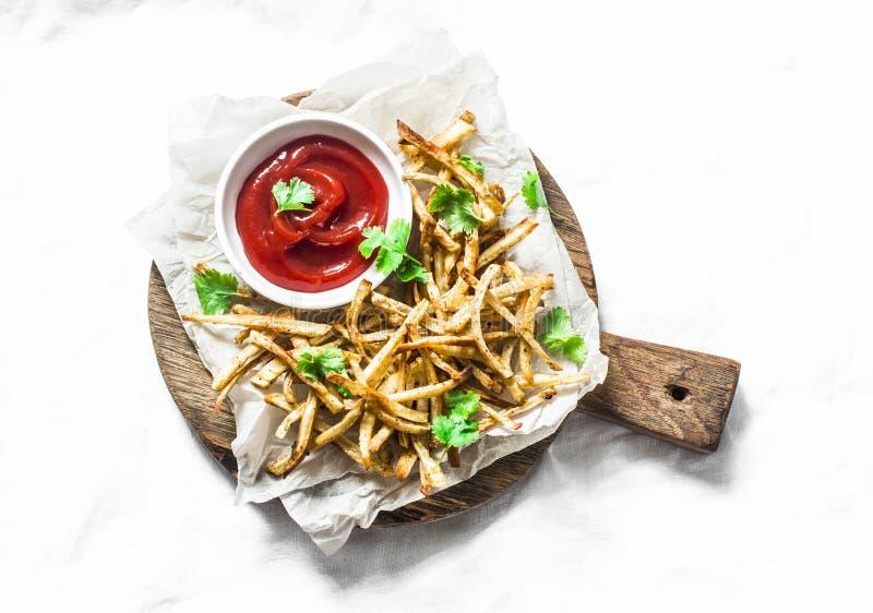 Patatas fritas cocidas de las pastinacas y salsa de tomate hecha en casa en la tabla de cortar - bocados vegetarianos sanos en fo fotografía de archivo libre de regalías