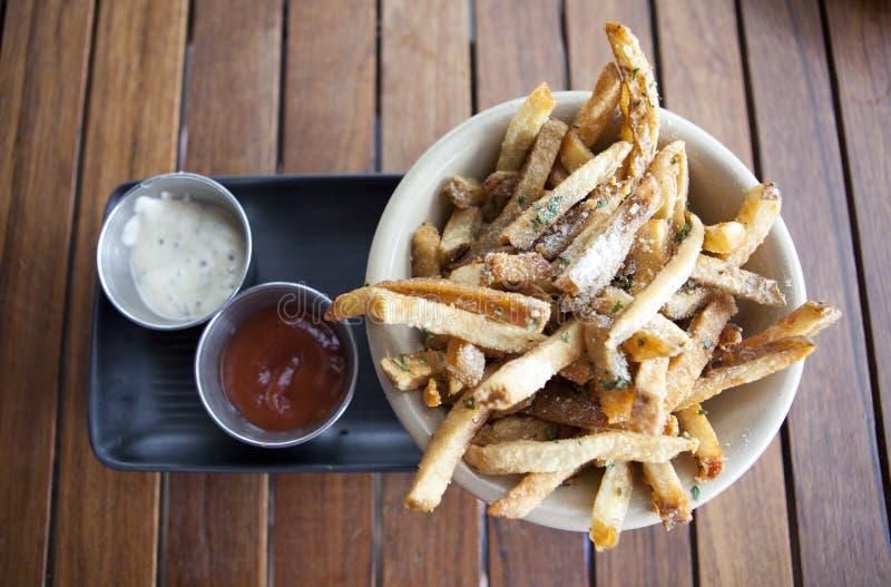 Patatas fritas con las salsas de inmersión imagenes de archivo