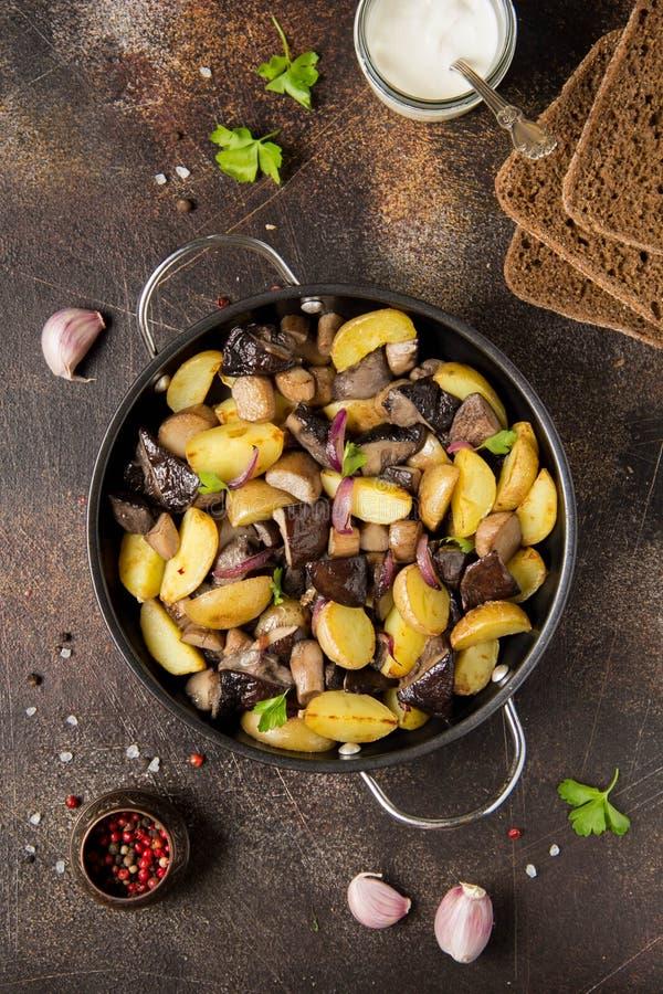 Patatas fritas con las setas, el boleto, las cebollas y la crema agria del bosque Plato rústico en el sartén, comida vegetariana  foto de archivo libre de regalías