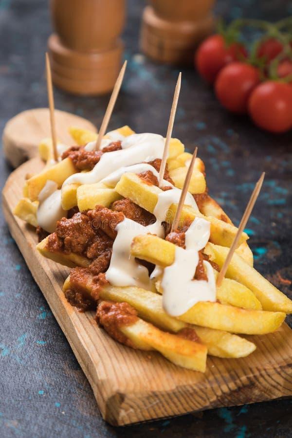 Patatas fritas con salsa picada de carne imagenes de archivo