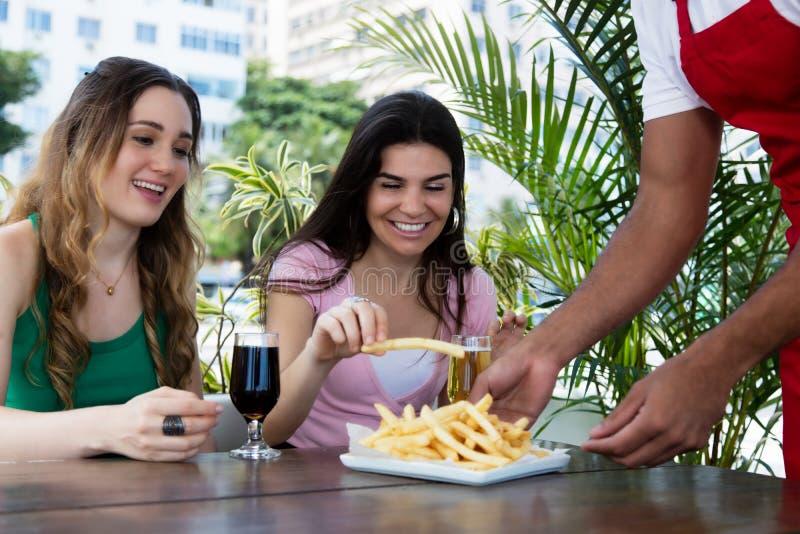 Patatas fritas de la porción del camarero a las huéspedes imagen de archivo libre de regalías