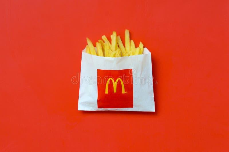 Patatas fritas de mcdonald en pequeña bolsa de papel en fondo rojo brillante imagen de archivo libre de regalías
