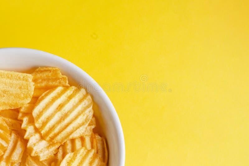 Patatas fritas de patata onduladas en un plato blanco sobre un fondo amarillo hermoso parte de la placa grande espacio libre en b imágenes de archivo libres de regalías