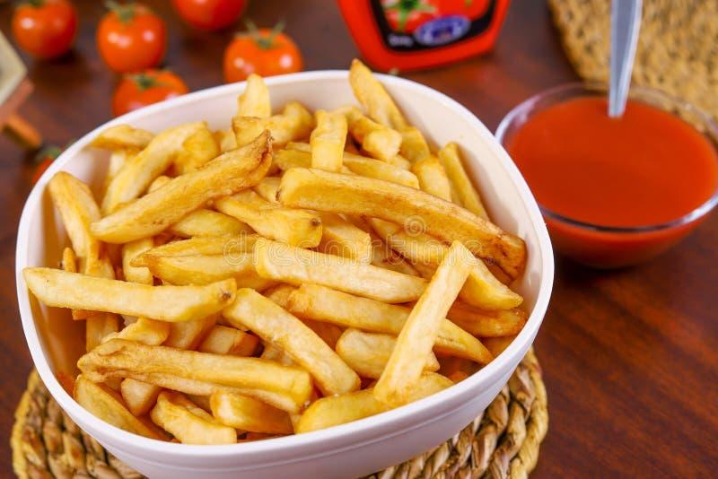 Patatas fritas en el cuenco blanco en un cojín trenzado en la tabla de madera con el tomate y la salsa de tomate al lado de ella imagen de archivo libre de regalías
