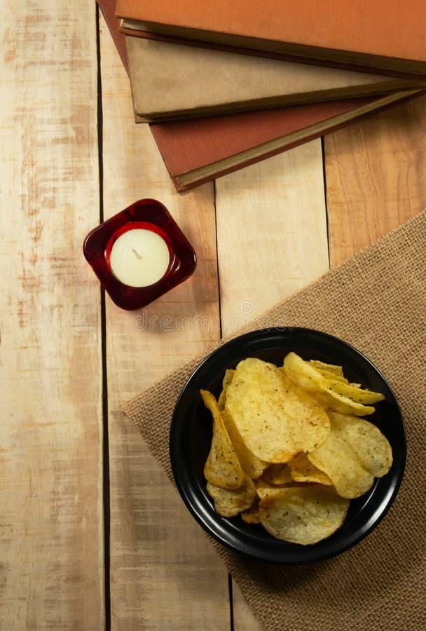 Patatas fritas en un cuenco negro, velas del aromatherapy y libros en un piso de madera imagen de archivo