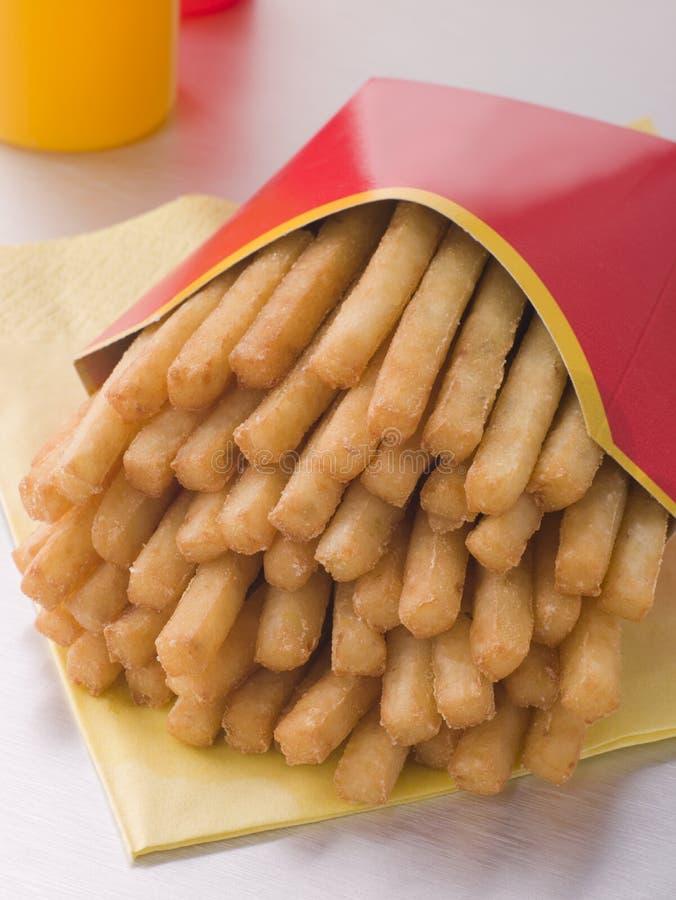 Patatas fritas en un rectángulo con las botellas de la salsa foto de archivo libre de regalías