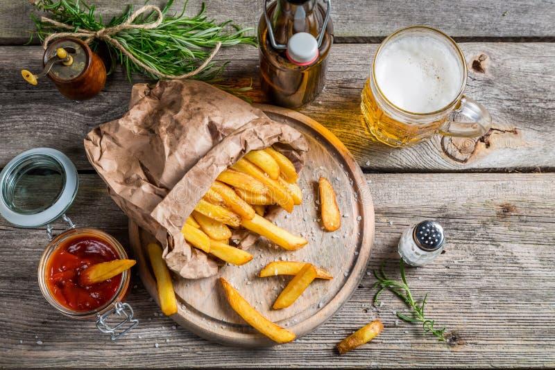 Patatas fritas frescas servidas con la cerveza fotografía de archivo