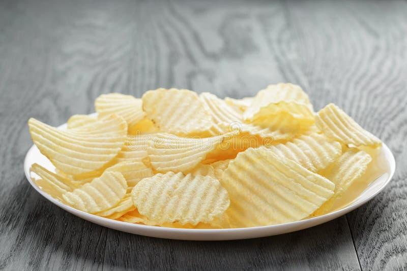 Patatas fritas onduladas en la placa blanca en la tabla de madera fotografía de archivo
