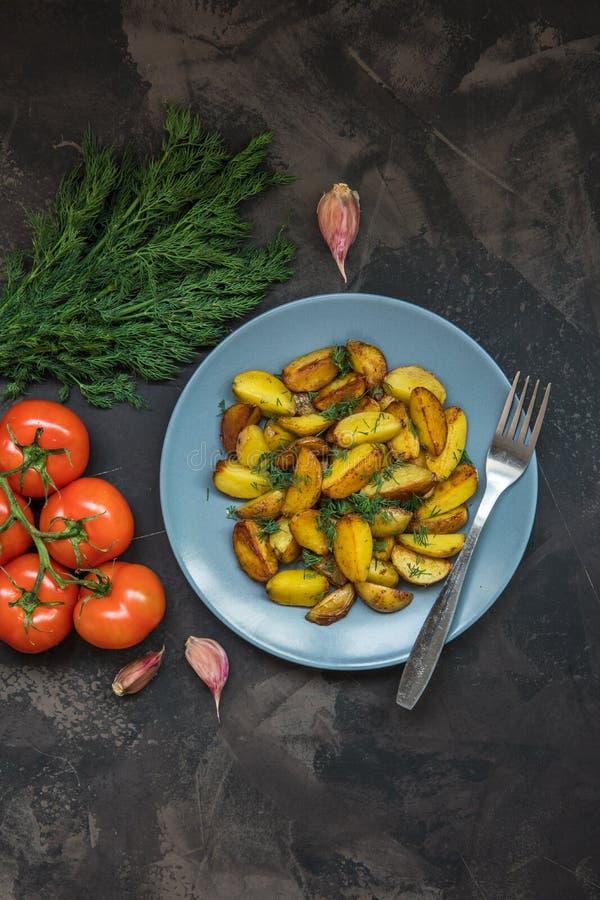 Patatas fritas, verde, tomates y ajo del bebé en un backgr oscuro foto de archivo