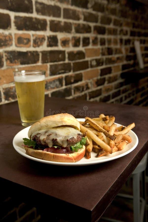Patatas fritas y cerveza del cheeseburger imagen de archivo libre de regalías