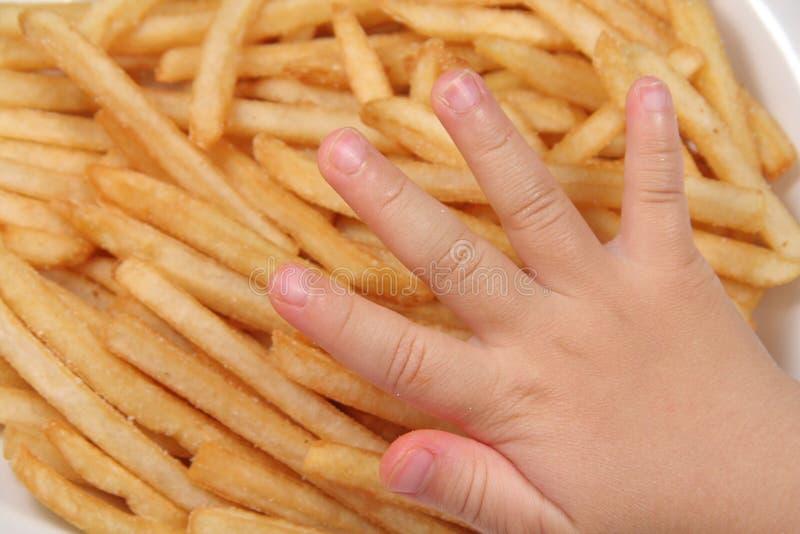 Patatas fritas y mano del niño imágenes de archivo libres de regalías