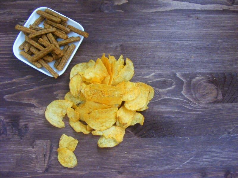 Patatas fritas y rebanadas de pan seco en la tabla de madera rústica foto de archivo libre de regalías