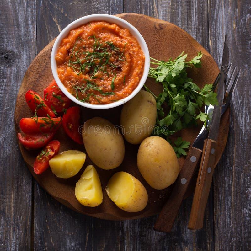 Patatas jovenes hervidas en una cáscara con el caviar del calabacín, las especias, los tomates del ffresh y el perejil foto de archivo