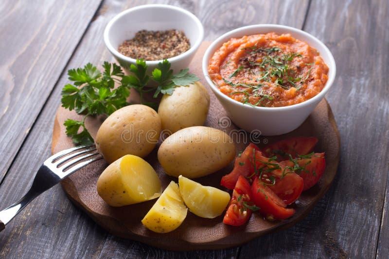 Patatas jovenes hervidas en una cáscara con el caviar del calabacín, las especias, los tomates frescos y el perejil imagen de archivo libre de regalías