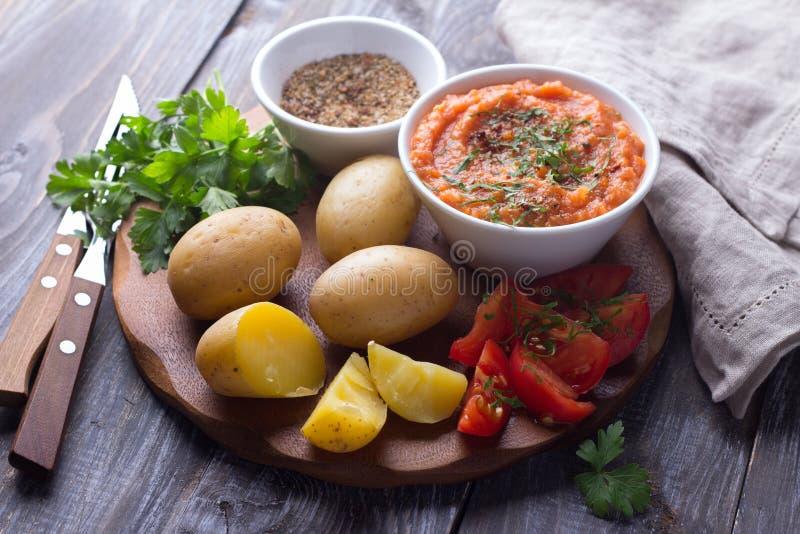 Patatas jovenes hervidas en una cáscara con el caviar del calabacín, las especias, los tomates frescos y el perejil imágenes de archivo libres de regalías