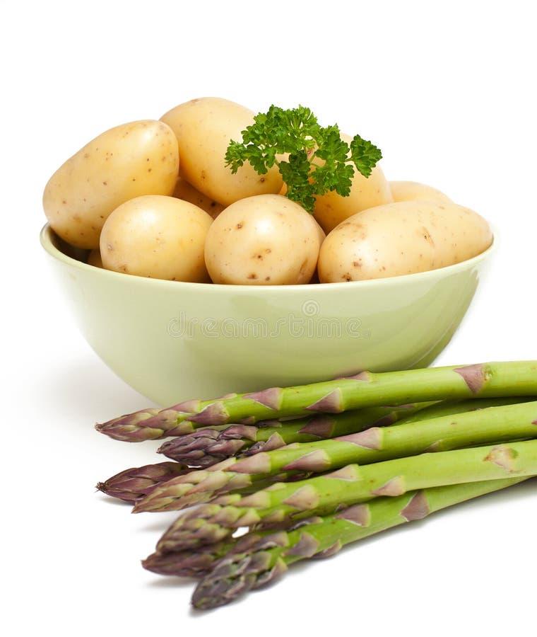 Patatas jovenes y espárrago verde imagen de archivo