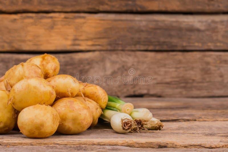 Patatas orgánicas crudas y cebolla verde de la primavera imagen de archivo