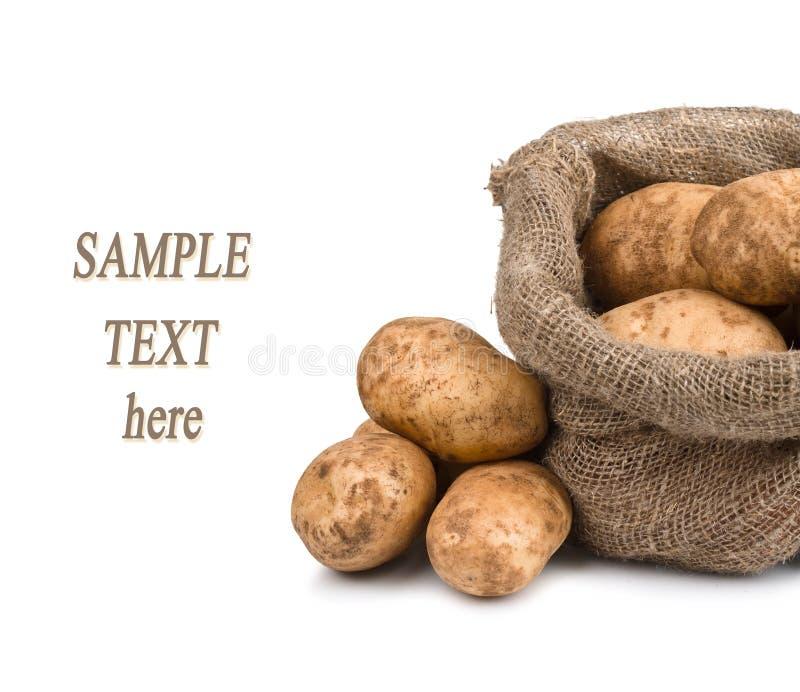 Patatas sin procesar en bolso de arpillera con el texto de la muestra foto de archivo libre de regalías
