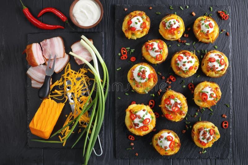 Patate al forno caricate con formaggio grattugiato fotografia stock libera da diritti
