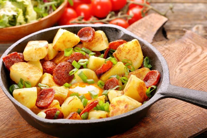 Patate al forno con il chorizo della salsiccia e l'uovo fritto sulla padella immagini stock libere da diritti