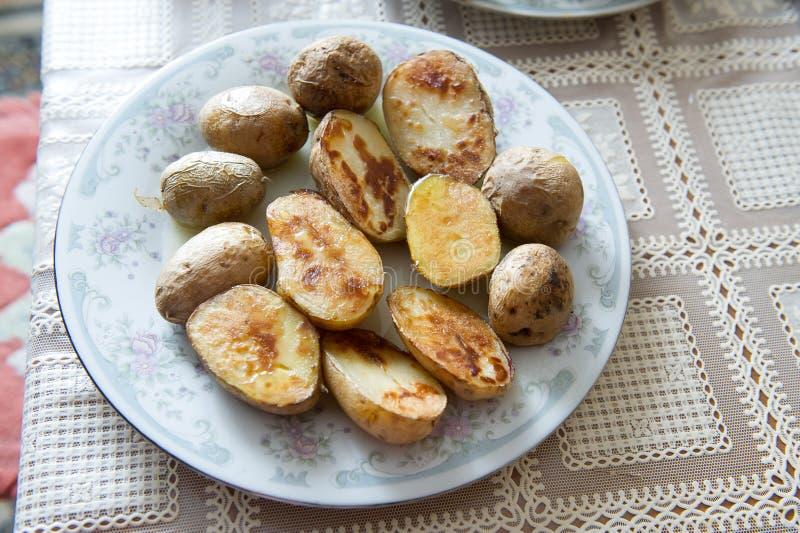 Patate al forno russe tradizionali con la buccia con olio vegetale su un piatto con un ornamento grigio fotografia stock