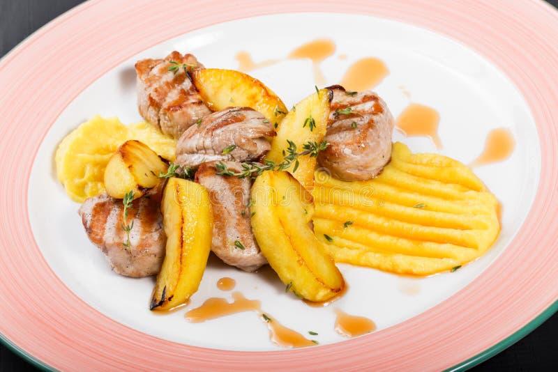 Patate arrostite con carne di pollo e le erbe in piatto su fondo di legno scuro Piatti caldi della carne fotografie stock libere da diritti