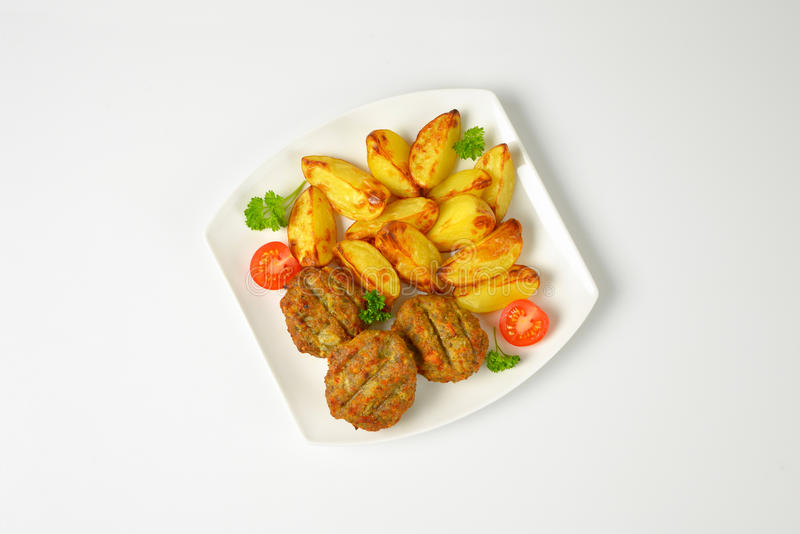 Patate arrostite e polpette fritte immagine stock