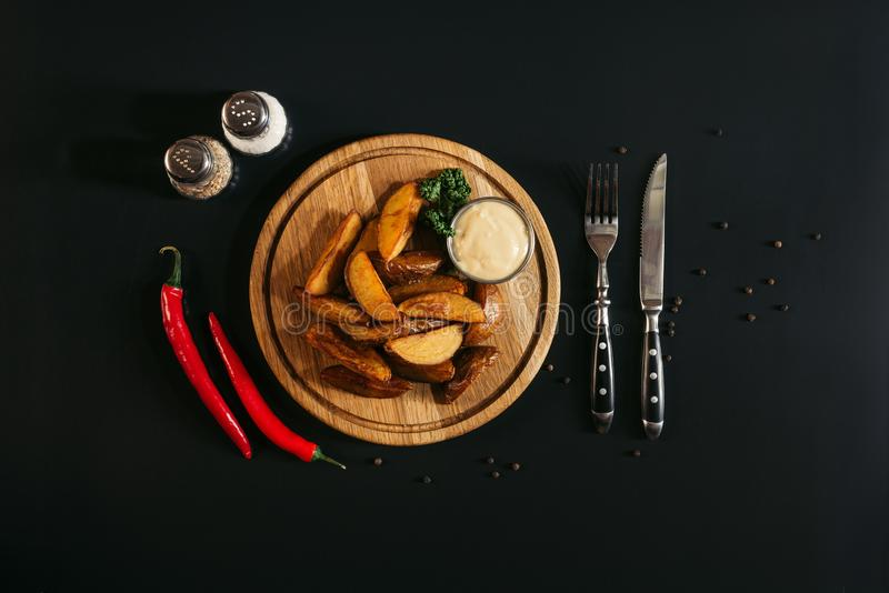 patate arrostite saporite con salsa sul bordo di legno, sulle spezie, sui peperoncini e sulla forcella con il coltello fotografia stock libera da diritti