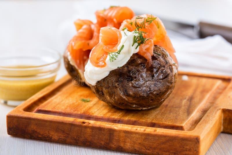 Patate bollite con la buccia con formaggio a pasta molle ed il salmone affumicato immagine stock libera da diritti