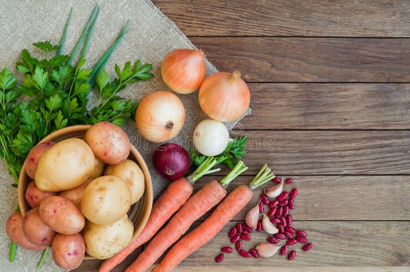 Patate, carote, cipolle sul licenziamento e tavola di legno immagini stock libere da diritti