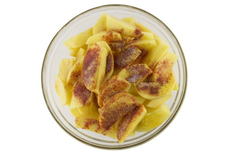 Patate crude con le spezie affettate in una ciotola trasparente Ingredienti per produrre le patate deliziose Cottura delle patate fotografie stock