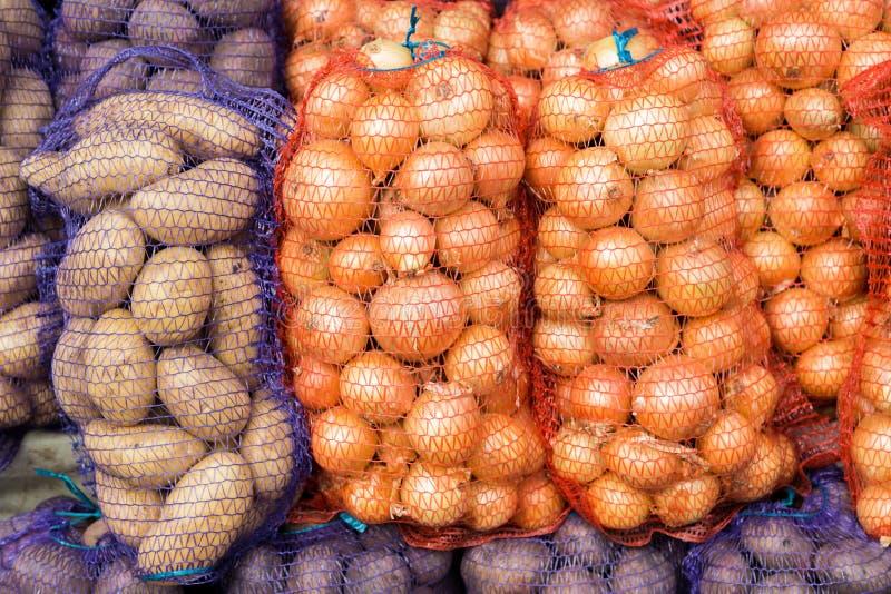 Patate e cipolle nella maglia sul mercato fotografia stock