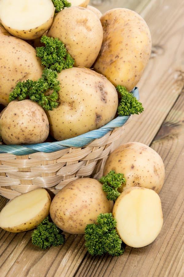 Patate e prezzemolo freschi in un canestro fotografia stock
