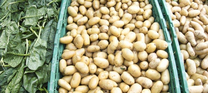 Patate e spinachs da vendere ad un mercato immagine stock