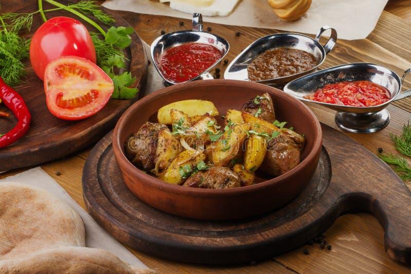 Patate fritte con carne in ciotola marrone su una tavola immagini stock libere da diritti