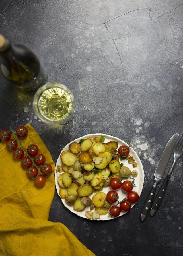 Patate fritte con i funghi, la cipolla ed i pomodori ciliegia a fondo nero immagine stock libera da diritti