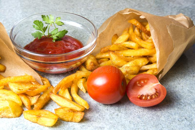 Patate fritte, patate fritte con ketchup e pomodori sui precedenti di granito grigio-blu fotografia stock libera da diritti